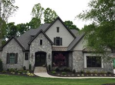 ARH Plan Asheville 1131F (Exterior 42) Stone: Dove Gray (gray mortar) Brick: Painted SW7023 Requisite Gray, Roof: Grand Manor Gatehouse Slate, Metal Roof: Medium Bronze, Soffits/Fascia/Trim: SW7675 Sealskin, Window Frames: Dark Bronze, Shutter/ Columns/ Front Door Stain/ Garage Door Stain: SW3542 Charwood, Entry Porch: Daltile Ayers Rock Majestic Mound,