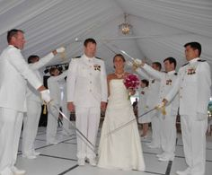 In this breaktaking all-white scene, a bride and groom walk through a military salute commemorating their wedding. In his dress whites, the groom looks down at his new wife, whose simple strapless gown is complemented by an intricate crystal necklace and a bouquet of fuschia pink peonies and lilies. Their wedding reception, held in a pristine white tent on the grounds of the Chesapeake Beach Resort in Islamorada FL, featured The John Parker Band. http://www.jpband.com/weddings.html
