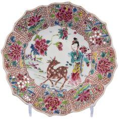 Coupelle peinte dans les émaux de la famille rose représentant Hsi Wang Mu – Reine Mère de l'Ouest en porcelaine de Chine de la Compagnie des Indes d'époque Yongzheng Le décor simulant une fleur de lotus, avec une aile chantournée, peint au centre d'une jeune femme et d'un cerf parmi des fleurs de pivoines. L'aile est peinte de huit réserves contenant des pivoines, des chrysanthèmes, des lotus, des bambous et des prunus sur un fond d'oeufs de poisson.