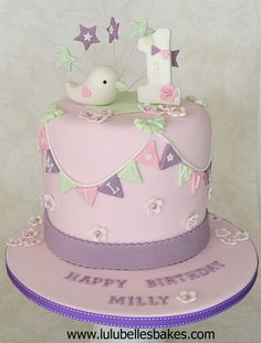 6 layer rainbow cake topped with sugar paste bird, stars and No. 1 and decorated with pretty bunting