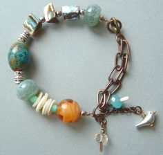 little bird - aqua gemstone - vintage pearl buttons - abalone - golden glass - assymetrical bracelet. $35.00, via Etsy.