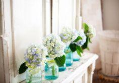 Blue mason jars filled with hydrangeas and lemon slices <3