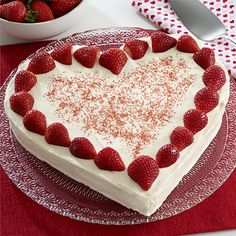 Heart-shaped strawberry cake topped with a creamy cream cheese and vanilla pudding frosting and fresh strawberries for strawberries and cream cake