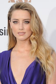 Slightly undone is the new chic. Heard makes a case for her signature side-parted swoop and messy waves on the red carpet. To achieve the '70s-inspired look yourself, simply wrap chunky pieces around a curling iron, then fluff out with a boar bristle brush.   - MarieClaire.com