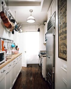 Kitchen Photo - A kitchen with butcher-block countertops, white cabinetry, and stainless-steel appliances