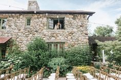 Rustic Summer outdoor wedding ceremony set-up- rustic wooden cross-back chairs, bistro lights, natural floral and greenery backdrop against stone mansion. Willowdale Estate is a weddings and events venue on in New England. WIllowdaleestate.com | Lena Mirisola Photography