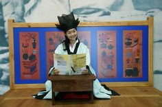 """Seonsaengnim at Seoul Museum of Education - In this photo, a girl poses in a Hunjang (costume) as a teacher/seonsaengnim (선생님) in an old classroom called a """"Seodang."""" The """"Seodang"""" were private village schools providing education of Chinese classics to males age 7-20."""
