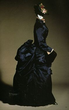 5. Walking Dress (c. 1884) of the third bustle style period, with a high bustle that is more extreme than before. Also, the dress covers the woman up to the neck.