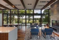 The house is sited on wooded plateau overlooking a wetland and lake beyond.