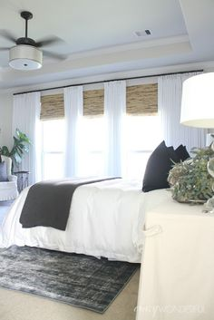 white drapes and bamboo shades, white bedding, overdyed rug, neutral bedroom