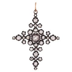 """Early Victorian Old Mine Cut Diamond Cross. Silver over gold Victorian cross pendant, 2.25 by 1.75 inches without the bale, set with thirty two old mine cut diamonds that weigh approximately 3 carats in total. Each stone is set in a """"belcher"""" style setting, creating a distinctly antique aesthetic that remains fashionable and relevant. Suspended from an 18 inch long antique gold chain. c 1850"""