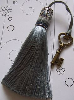 A misty light gray, this exquisite little handmade tassel is an original design, a lovely size for hanging on your wardrobe door handle, drawer, or key. The silky light gray threads have a tactile quality and hang beautifully. The beaded cuff uses glass seed beads woven using peyote stitch, in shades of silvery gray in a variety of finishes. The tassel has an antiqued silver metal bead cap, Sterling silver twists and a medium gray ribbon. The length of the tassel from the bead cap to the…