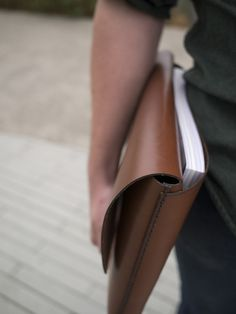 "Minimally designed and meticulously constructed, the Donner Folio works equally well as an understated briefcase or as a sturdy computer case. A single long piece of leather creates the main sleeve, which can accommodate key documents, a 13"" macbook and then some. The rear pocket provides enough additional depth to comfortably hold a presentation or magazine."
