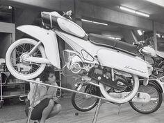 Bromfietsen, snorfietsen, solex. Mejuffrouw Ina van Kooten leidt de bromfietszaak van haar vader, hier bekijkt zij de DKW-Hummel bromfiets op de stand in de RAI, Nederland 1961.  English: Owner moped shop admiring moped. The Netherlands, Amsterdam, 1961.
