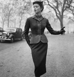 Model sporting a tailored suit by Simon Massey with a contrasting border on the jacket (November 1953).