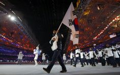 South Korea's flag-bearer Lee Kyou-hyuk leads his country's contingent during the opening ceremony of the 2014 Sochi Winter Olympic Games February 7, 2014. (REUTERS/Brian Snyder)