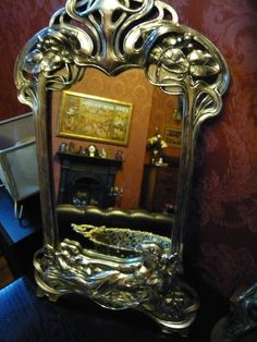 Art Nouveau style mirror from Past Times.  I birthday present a few years ago.  It's near the front door and checking I look presentable before leaving the house.  The reclining lady is very cute. :)
