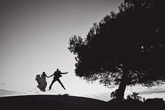 aaaa love this photo. jumping silhouette next to huge tree on a hill. <3