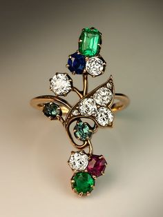 An Antique Art Nouveau Gemstone Flower Ring. Russian, made in Kazan between 1908 and 1917. The 14K gold ring is designed as a stylized flower set with six bright white and sparkling old cushion cut diamonds, two rose cut diamonds, two emeralds, two alexandrites, one ruby and one sapphire.
