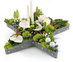 Christmas Advent Star arrangement an alternitive to a Advent Wreath. Contains Lilies, Feeling Green, Baubles and lots of other interesting details. Christmas Flower Arrangements, Christmas Flowers, Floral Arrangements, Christmas Holidays, Christmas Decorations, Christmas Ornaments, Christmas Star, Christmas Flower Delivery, Christmas Pebble Art