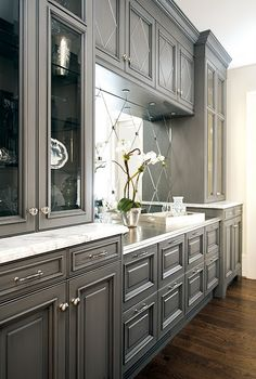 Silver/Gray cabinets and a mirrored back splash