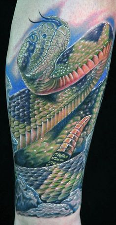 Realistic green snake tattoo on leg
