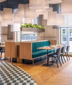 a brass cage-like cabinet wrapped organizes the restaurant, bar and lobby areas of the mama makan grand cafe in amsterdam