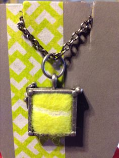 DIY Tennis Ball Necklace. Urban Chic. Cool. Simple. I made these for the graduating seniors on the high school tennis team. The square *holder* originally was intended for a picture. I removed the glass and slid in a fitted piece of tennis ball.