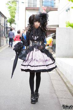 This is Alumi, a fan of the gothic Japanese fashion brand h.Naoto who is often seen around Harajuku. Alumi is wearing a gothic lolita outfit with a Frill dress and top paired with a h.NAOTO Blood jacket. Her purse is from Artherapie and her heeled brogues are Yosuke. She is also wearing a corset from h.NAOTO Steam, a Hangry & Angry headdress and a ruffled parasol. (Tokyo Fashion, 2014)