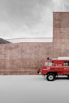 A fire station made of red concrete in South Tyrol by Pedevilla architects looks like straight out of a fairytale