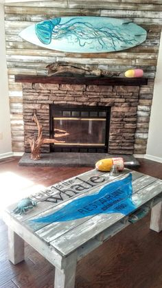 My husband built a gorgeous accent wall out of shipping crates from our local water company. I whitewashed it, and it really brings out the mantle. We added a painted surfboard and it really ties in with our new coffee table. Love!
