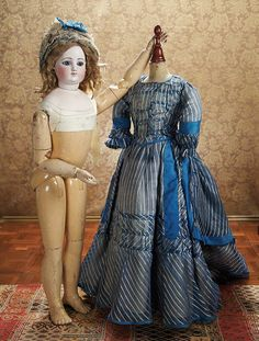 Grand-Size French Bisque Poupee with Deluxe Wooden Articulated Body, With silk gown and undergarments,ruffled lace and blue silk matching bonnet, circa 1865
