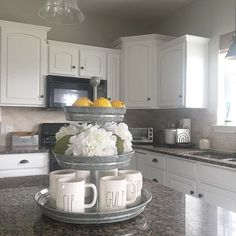 Farmhouse style kitchen, galvanized steel, white cabinets and Rae Dunn.