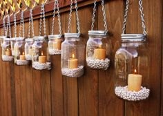 DIY: Hanging jar lanterns.  The page gives you a link for the chained lid hangers pre made.  I say use an awl and put your own holes in the lids then run chain or whatever works through the holes.  This page has several mason jar crafts. Brilliant really.
