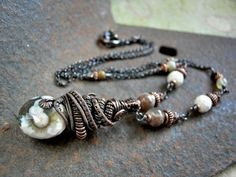 An earthy elegant distinctive necklace of elaborate oxidized copper wire wrap & ocean jasper in rich, neutral colors.