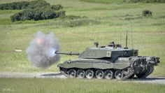 A Challenger 2 tank on Castlemartin Ranges in Pembrokeshire, Wales fires a 'Squash-Head' practice round.