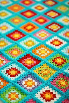 granny square inspiration for a blanket in bright colors. Warm reds, orange and yellows on the inside and border with aqua for a cheerful color scheme.