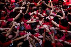 "Members of the Castellers of Barcelona join their hands to start making their ""castell"" or human tower in the Barcelona neighborhood of Gracia, Spain, on May 19, 2013. A ""castell"" is a human tower traditionally built during festivals in many places in Catalonia. At these festivals, several ""colles"" or teams compete to build the most impressive towers they can. (Photo by Emilio Morenatti/Associated Press) http://avaxnews.net/fact/Collapse_of_the_Human_Tower_Castell.html"