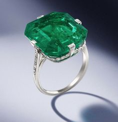 An emerald and diamond ring, by Van Cleef & Arpels, 1920 The octagonal step-cut emerald, weighing 18.67 carats, within a delicate mount millegrain-set with single-cut diamonds and engraved decoration