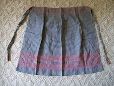 Vintage Gingham Apron. This is a Half Apron with Red Chicken Scratch Embroidery made with Black and White Gingham fabric. This apron measures 23 1/2 x 23 inches the ties are 1 1/2 x 21 1/2 inches each. Has small pleats at the top, has very pretty and detailed hand embroidered . It is in great condition, one very small hard to see hole, no spots.