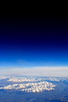 Snowy Mountains, clouds, blue sky far below
