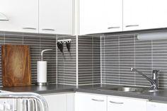 harmaat laatat/kaakelit,valkoiset keittiönkaapit,keittiö,keittiön välitila,välitila
