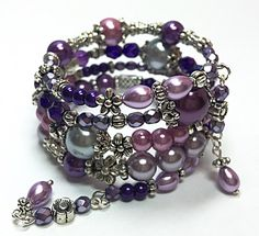 This handmade beaded memory wire bracelet is made with varying shades of purple and pink pearl glass beads and purple glass beads. Purple