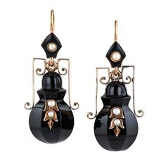 These intriguing antique amphora motif earrings were originally worn during the Victorian period as mourning jewelry. These days however they make a sophisticated fashion statement and a dramatic compliment to your basic black wardrobe. The three-dimensional amphoras are hand carved in onyx with rose gold and seed pearl decorative overlays; the fanciful handles are crafted in 9 karat rose gold and the tops are rendered in black enamel and seed pearls, circa 1875