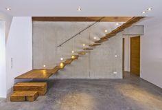 Extravagantes Treppenhaus aus Sichtbeton und frei schwingenden Holzstufen