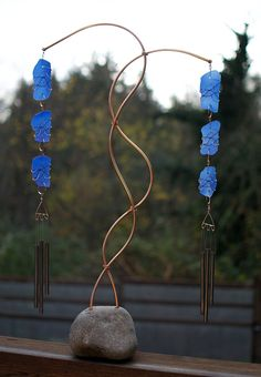 A freestanding natural Pacific beach stone base wind chime— naturally beautiful. This wind chime has a large Pacific beach stone base. The copper supports are embedded right into the stone base. The a