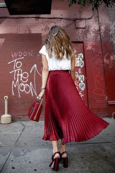 The weekend is just around the corner, thankfully. Luckily, we've been collecting weekend looks for the fall and winter. This blogging babe knocked it out of the park in a classic outfit that's been updated with trendy pieces. She paired a blush toned bomber jacket with a red pleated midi skirt and slipped on some high heeled sandals for added effects. Coffee not included.