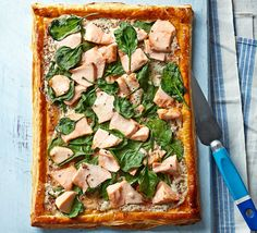 A light lunch or dinner party starter of puff pastry topped with mustard crème fraîche, flaked salmon fillets, and baby spinach