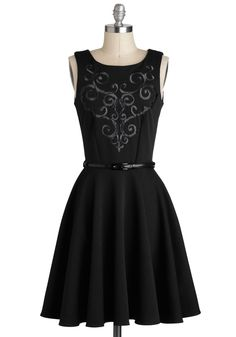 Sleeveless black tank dress with scoop neck, bodice front & rear princess darts, V-shaped black filigree satin-stitch embroidery on front bodice, black patent faux-leather skinny belt accenting natural waist, knee-length 3-piece A-line skirt, and back zipper. 93% polyester/7% elastane, from ModCloth, $79.99