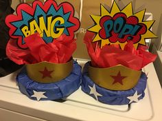 Wonder Woman Centerpiece    Materials Used:   1 Foam Floral Circle    2 sheets each of Red and Blue Tissue Paper   2 Signs from local craft store   2 Tiara's from online similar to Wonder  Woman's   3 Dowel Rods cut in half   1 sheet of white cardstock with outline of stars to cut (5 stars per round)   Scotch Tape